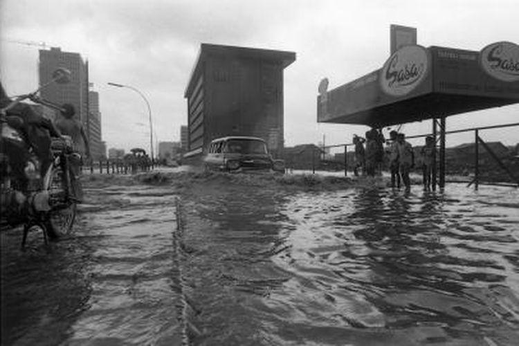 Hujan yang sudah mulai malam sebelumnya, ternyata membawa ekor dipagi harinya -- banjir. Dibeberapa tempat di Ibukota Rabu pagi kemarin mengalami banjir ini. Bahkan dikata genangan air di jalan Thamrin lebih besar dan dalam bila dibandingkan dengan yang sudah-sudah. Banyak kendaraan bermotor mogok, hingga lalu lintas di jalan tersebut macet. Gambar menunjukkan betapa besarnya ,,gelombang yang tesera oleh kendaraan bermotor ini. Terkait berita Kompas, 05-03-1976