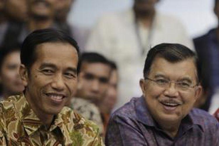 Pasangan calon presiden dan wakil presiden, Joko Widodo (Jokowi) dan Jusuf Kalla (JK) hadir pada pengumuman rekapitulasi hasil penghitungan perolehan suara peserta Pemilu Presiden dan Wakil Presiden 2014 di Kantor Komisi Pemilihan Umum (KPU), Jakarta, Selasa (22/7/2014) malam. KPU menetapkan Jokowi-JK sebagai pemenang Pilpres 2014 dengan memperoleh 53,15 persen suara. KOMPAS IMAGES/KRISTIANTO PURNOMO