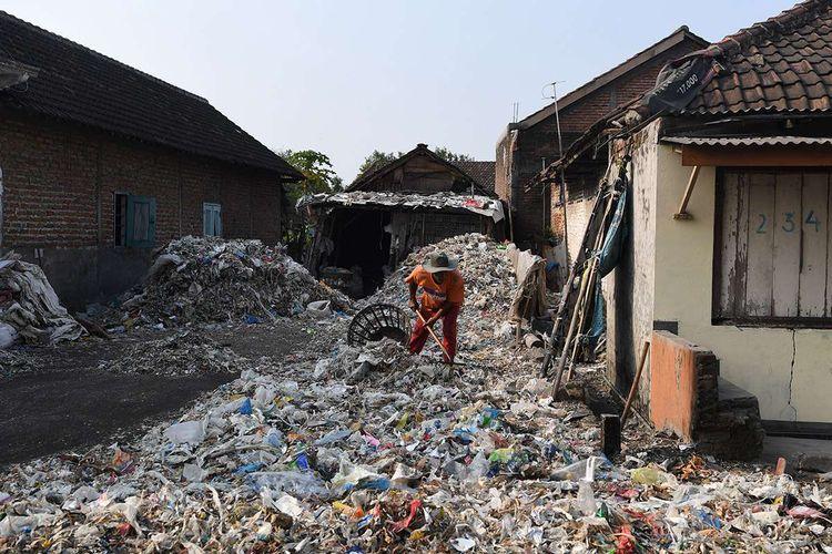 Foto dirilis Selasa (6/8/2019), menunjukkan seorang warga memilah tumpukan sampah plastik impor sekitar rumahnya di Desa Bangun di Mojokerto, Jawa Timur. Indonesia diperkirakan setiap harinya menerima sedikitnya 300 kontainer sampah yang sebagian besar menuju ke Jawa Timur, diduga dampak kebijakan China yang menghentikan impor sampah plastik dari sejumlah negara di Uni Eropa dan Amerika.