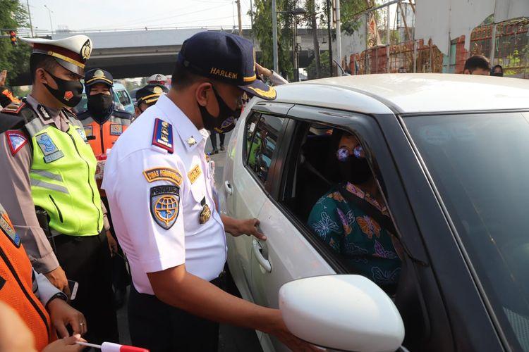 Petugas mensosialisasikan penerapan kembaki sistem ganjil-genap di ruas Jalan Gunung Sahari, Jakarta Utara