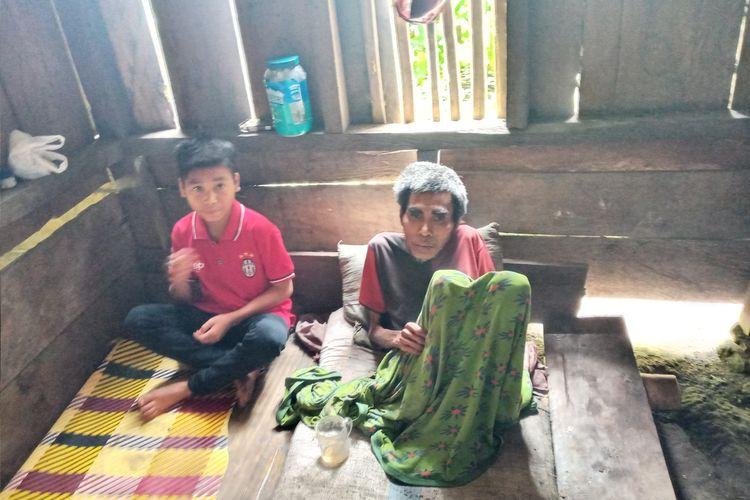 Bocah 12 tahun, Risalianus Aja duduk bersama ayahnya Benediktus Poseng (49) yang derita lumpuh di kamar sempit di rumah mereka di Kampung Kotatunda, Desa Nanga Meje, Kecamatan Elar Selatan, Kab. Manggarai Timur, NTT, Rabu, (3/3/2021). (KOMPAS.com/MARKUS MAKUR)