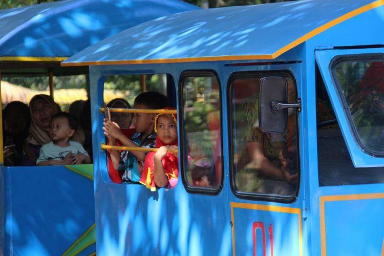 Pengunjung menaiki kereta di Taman Margasatwa Ragunan, Jakarta, saat libur hari raya Natal, Senin (25/12/2017). Tercatat hingga Senin siang, lebih dari 60.000 pengunjung memadati kebun binatang yang kerap dijadikan destinasi wisata saat musim liburan tersebut.