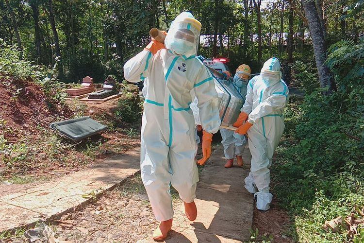 Salah satu tim relawan BPBD Wonogiri memakamkan jenazah secara protokol kesehatan covid-19 di Desa Sonoharjo, Kecamatan Wonogiri, Kabupaten Wonogiri, Jawa Tengah, Rabu (7/7/2021).
