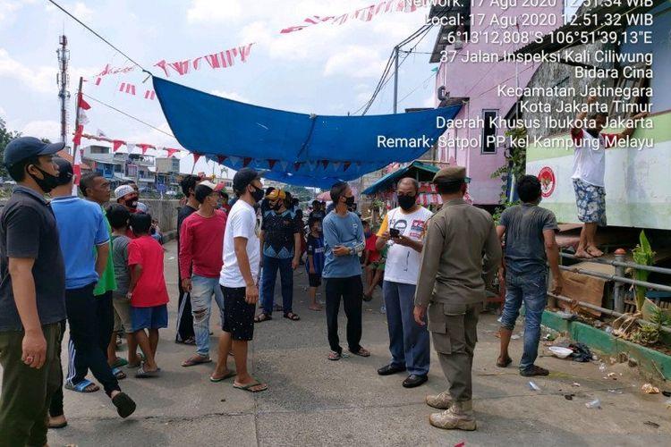 Petugas Satpol PP Jakarta Timur membubarkan kerumunan warga yang menjadi peserta serta penonton dalam agenda lomba 17 Agustus di Kampung Melayu, Jakarta Timur, Senin (17/8/2020).