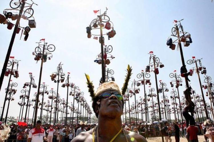 Seorang warga Papua menyaksikan kompetisi panjat pinang yang biasanya digelar ketika perayaan kemerdekaan Indonesia