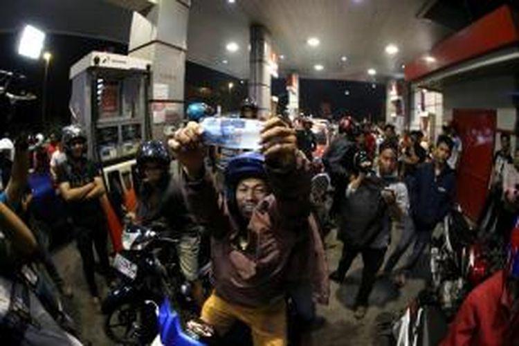 Warga antre membeli bahan bakar minyak (BBM) di sebuah SPBU di Makassar, Sulawesi Selatan, Selasa (18/11/2014) dini hari. Antrean panjang terjadi karena adanya pengumuman pemerintah tentang kenaikan harga BBM bersubsidi jenis premium dan solar masing-masing sebesar Rp 2.000 per liter terhitung mulai 18 November pukul 00.00 WIB.