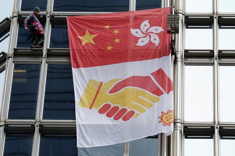 Pemanjat asal Perancis Alain Robert saat memanjat gedung bertingkat Cheung Kong Center di Hong Kong dan membentangkan bendera pesan perdamaian.
