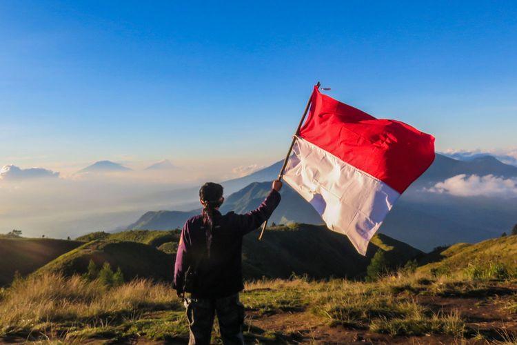 Seorang pendaki mengibarkan bendera merah putih di Gunung Prau.