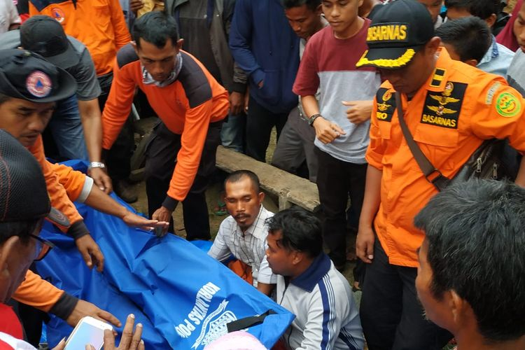 Petugas Basarnas Pekanbaru, BPBD dan masyarakat saat mengevakuasi jasad Muhamad Al Arifin, seorang bocah lima tahun yang diterkam buaya di sungai di Desa Morong, Kecamatan Sungai Lala, Kabupaten Inhu Riau, Minggu (14/4/2019).