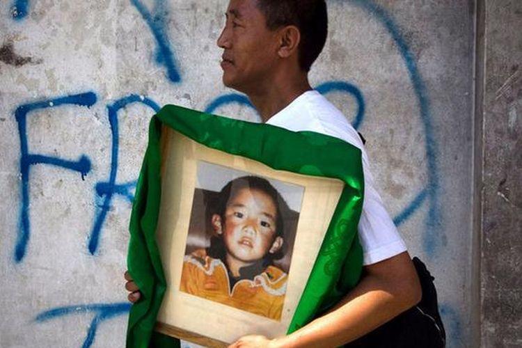 Seorang warga Tibet membawa foto terakhir Gendün Choekyi Nyima atau Panchen Lama ke-11, sebelum hilang diculik oleh pemerintah China.