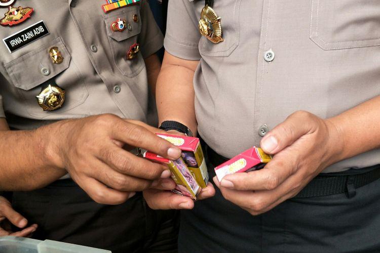 Polisi membandingkan bungkus rokok asli dan palsu salah satu merk dagang saat merilis kasus produksi dan penjualan rokok palsu di Mapolsek Setiabudi, Jakarta Selatan, Senin (12/2/2018). Sekilas, tak tampak perbedaan antara bungkus rokok yang asli dan palsu.