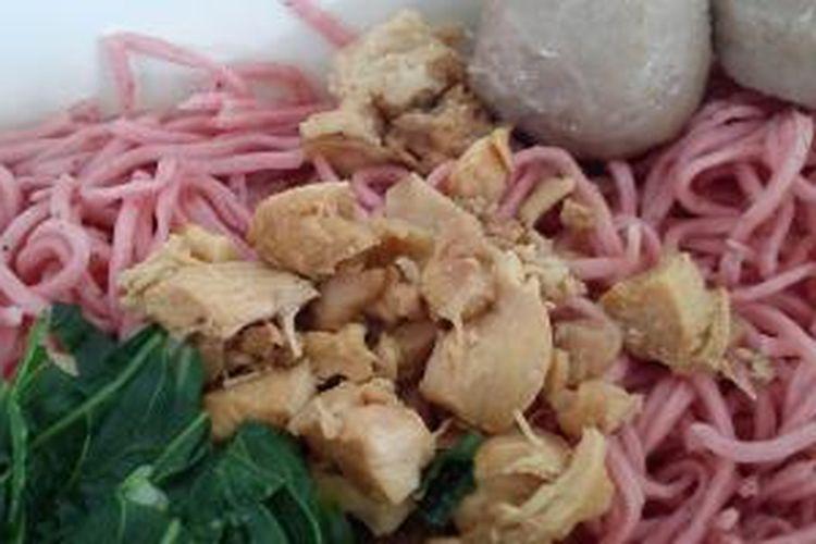Mie Ayam Buah Naga, mie berwarna merah dengan bintik hitam buah naga yabg bertekstur lembut dan kenyal memiliki rasa yang gurih. Disajikan dengan potongan ayam, sawi, dan dua buah bakso.