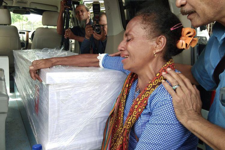 Salah seorang kerabat TKI Adelina, saat menangis dan memegang peti jenazah Adelina yang dimasukan ke dalam mobil jenazah di Bandara El Tari Kupang, Sabtu (17/2/2018)