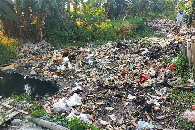 Tutupan sampah memenuhi aliran Kali Busa atau Kali Bahagia, Kecamatan Babelan, Kabupaten Bekasi.