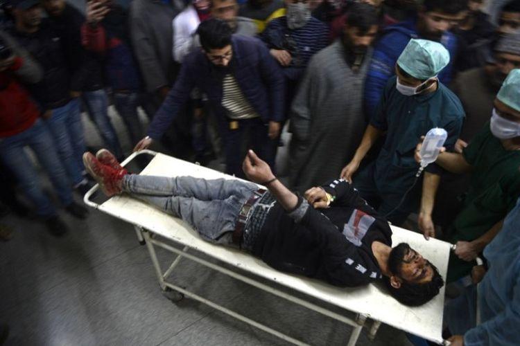 Personel medis membawa seorang pemuda yang terluka akibat tembakan peluru selama bentrokan dengan pihak berwenang, di Srinagar, India, Sabtu (15/12/2018). (AFP/Tauseef Mustafa)