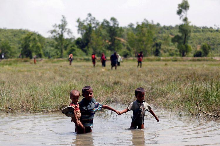 Anak-anak Rohingya berjalan melewati air saat mereka berusaha untuk masuk ke Bangladesh dari No Mans Land setelah sebuah tembakan terdengar dari sisi Myanmar, di Coxs Bazar, Bangladesh, Senin (28/8).
