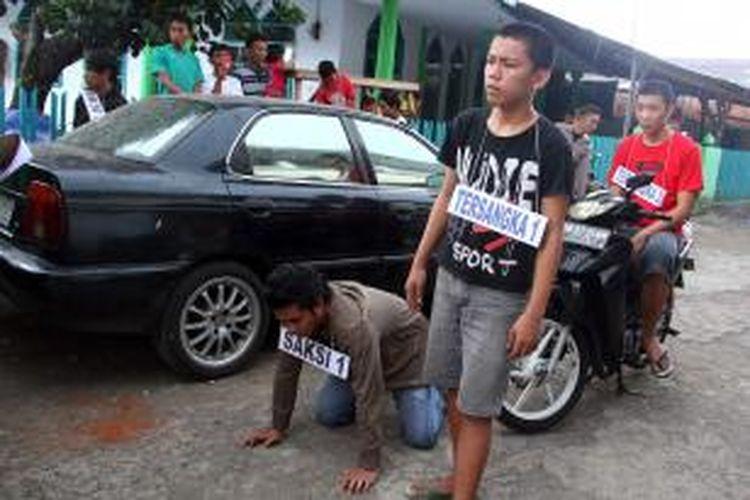 Para tersangka dan saksi sedang memeragakan adegan reka ulang terhadap kasus pembunuhan dengan panah wayer yang menewaskan korban di Manado.