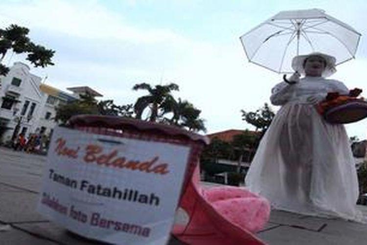 Sopiah memerankan karakter noni belanda saat menunggu pengunjung kawasan Kota Tua, Jakarta Barat, yang hendak berfoto dengan dirinya, Kamis (16/5/2013). Di akhir minggu, sebanyak 10 orang mencari rejeki dari pengujung Kota Tua dengan menampilkan karakter. Rata-rata dalam sehari mereka bisa mendapatkan uang antara Rp 200.000 - Rp 700.000.