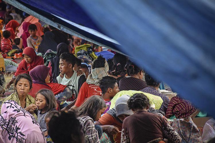 Sejumlah warga korban gempa berada di pengungsian di lapangan Desa Sajang, Kecamatan Sembalun, Selong, Lombok Timur, NTB, Minggu (29/7/2018). Para warga di Desa Sajang dan Desa Sembalun Bumbung memilih tidur di tenda pengungsian karena masih sering terjadinya gempa susulan yang menurut data stasiun Geofisika BMKG Mataram terjadi sebanyak 145 kali gempa susulan hingga terakhir pada pukul 17:45:04 Wita dengan magnitude 3.1.