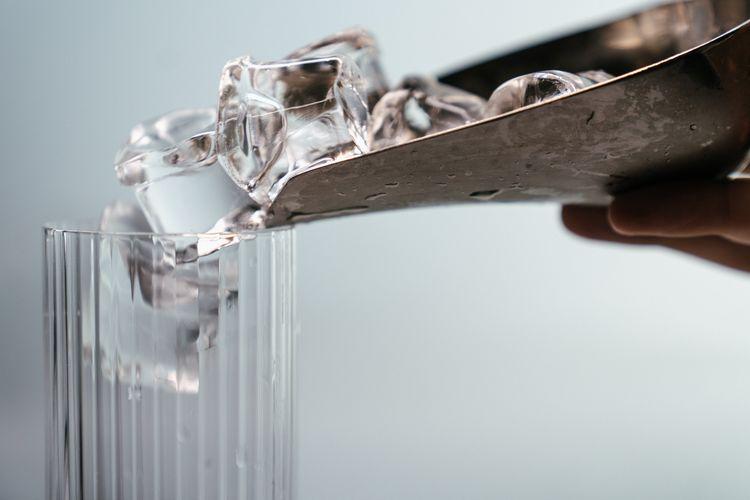 Ilustrasi es batu yang dituang ke dalam gelas.