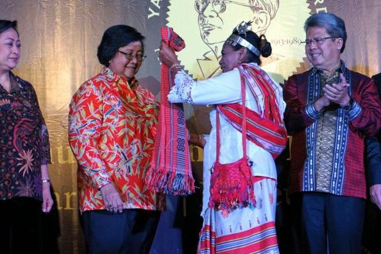 Aleta Baun atau akrab disapa Mama Aleta, saat memberikan kain tenun khas NTT kepada Menteri Siti Nurbaya saat penganugerahan Yap Thiam Hien award di Museum Nasional, Jakarta Pusat, Rabu (25/1/2017).