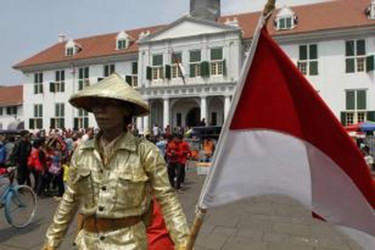 Manusia patung menghibur pengunjung di lapangan Taman Fatahillah di kawasan Kota Tua Jakarta Barat, Rabu (30/7/2014). Dua hari setelah lebaran, kawasan Kota Tua dipenuhi warga yang mengisi masa liburan bersama keluarga.