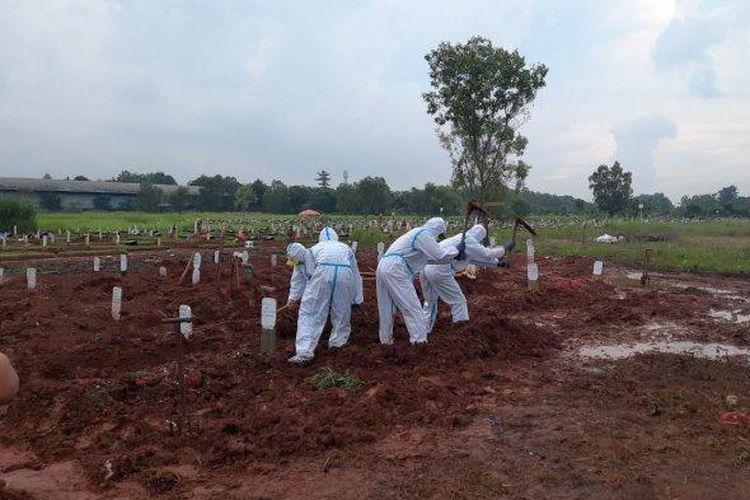 Petugas TPU Pedurenan di Kecamatan Mustikajaya, Kota Bekasi saat melakukan pemulasaraan jenazah pasien Covid-19.