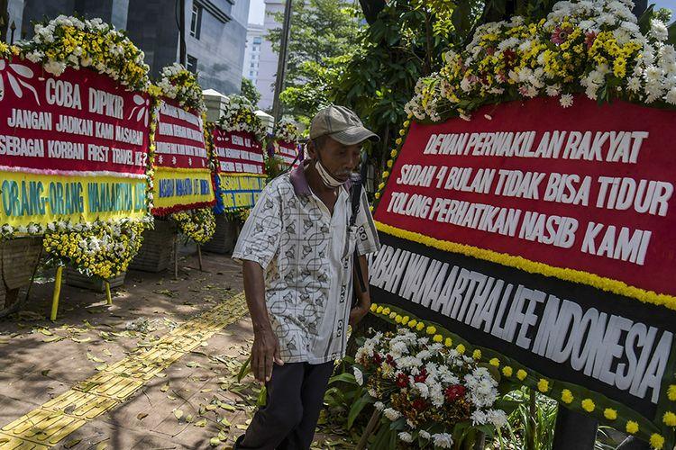 Warga melintasi karangan bunga di Pengadilan Tipikor, Jakarta, Rabu (3/6/2020). Karangan bunga tersebut berasal dari korban terdampak kasus asuransi Jiwasraya yang mengharapkan lembaga terkait untuk memberikan keadilan bagi mereka.