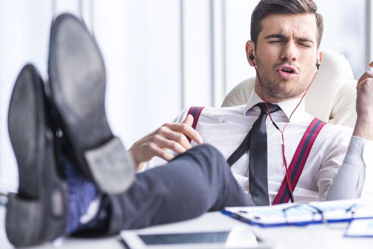 Seorang pria mendengarkan musik sata di kantor