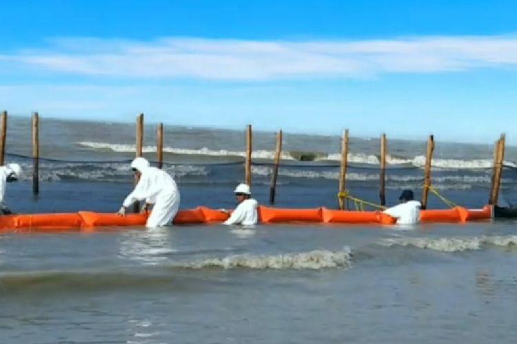 Petugas memasang oilboom shore line unutk menangkap tumpahan minyak yang terbawa hingga ke pantai  utara Pulau Jawa