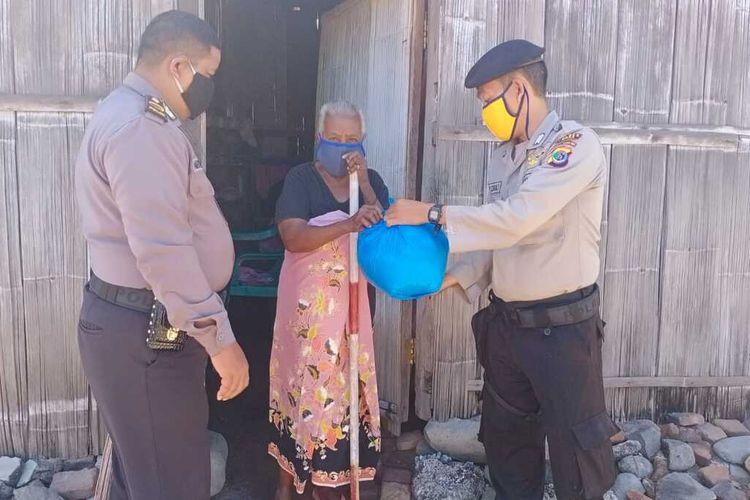 Foto : Anggota Polsek Alok, Kecamatan Alok, Kabupaten Sikka, NTT menyerahkan sembako kepada warga di Kelurahan Mandawat, Rabu (13/5/2020).