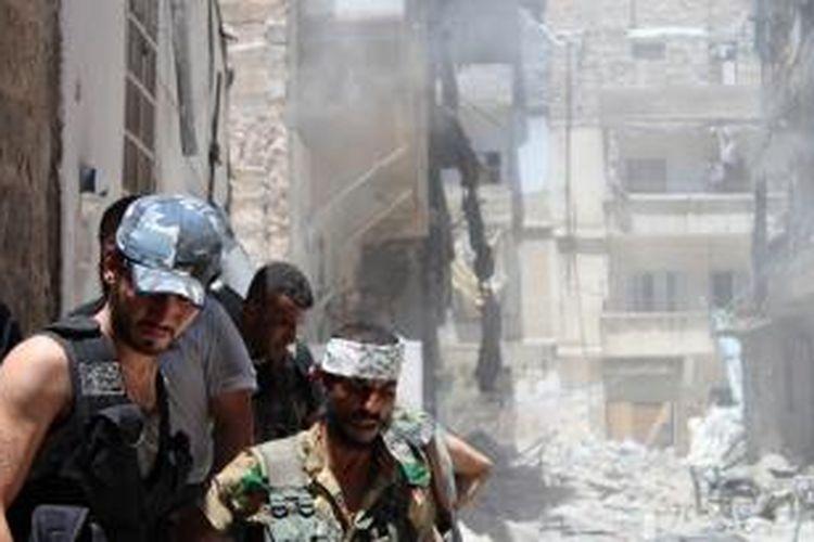 Pasukan pemberontak berkumpul di luar sebuah gedung yang mereka ledakkan untuk menghentikan aksi sniper pasukan pemerintah. Seorang tokoh senior oposisi dibunuh kelompok militan di kota Latakia, Suriah.