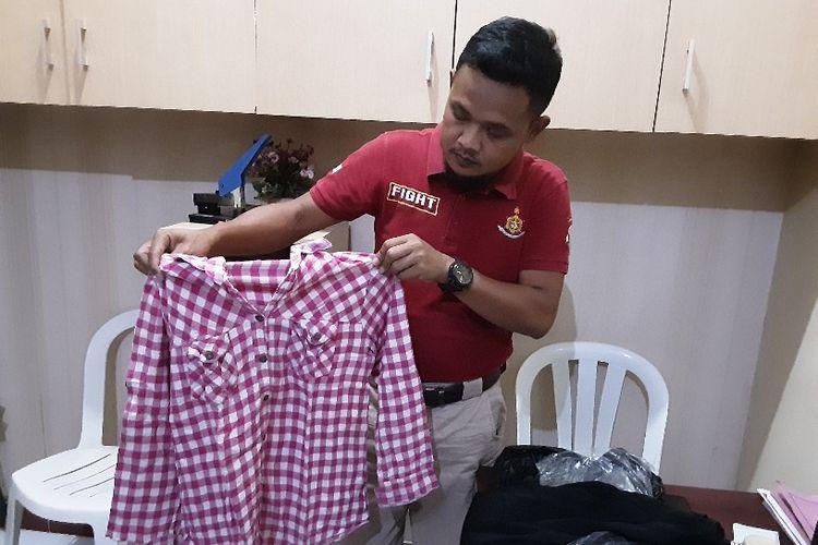 Anggota Polsek Tegal Barat, Rabu (18/9/2019) menunjukan pakaian SNM (16) gadis yang dicabuli pelaku yang dikenal lewat Facebook.
