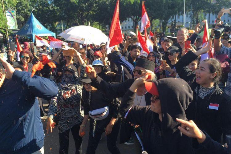 Massa yang menamakan diri Jakarta Bergerak, Suara Rakyat Bersatu menggelar aksi teatrikal lempar tomat sebagai bentuk kekecewaan terhadap Gubernur DKI Jakarta Anies Baswedan di Jalan Silang Merdeka Barat Daya, Monas, Selasa (14/1/2020).