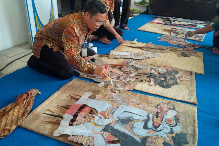 Petugas Museum Radya Pustaka Solo membersihkan koleksi wayang peninggalan PB II dan X di museum setempat di Solo, Jawa Tengah, Rabu (19/9/2018). Ngisis wayang rangkaian kegiatan Suro Bulan Kabudayaan Tahun 2018 yang digelar Museum Radya Pustaka sejak 12 September 2018 hingga 11 Oktober 2018.