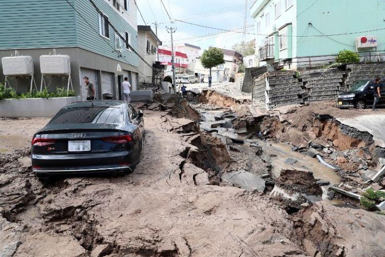 Sebuah mobil terlihat terjebak di jalan yang rusak akibat gempa di Sapporo, prefektur Hokkaido, Jepang pada Kamis (6/9/2018). (AFP/Jiji Press)