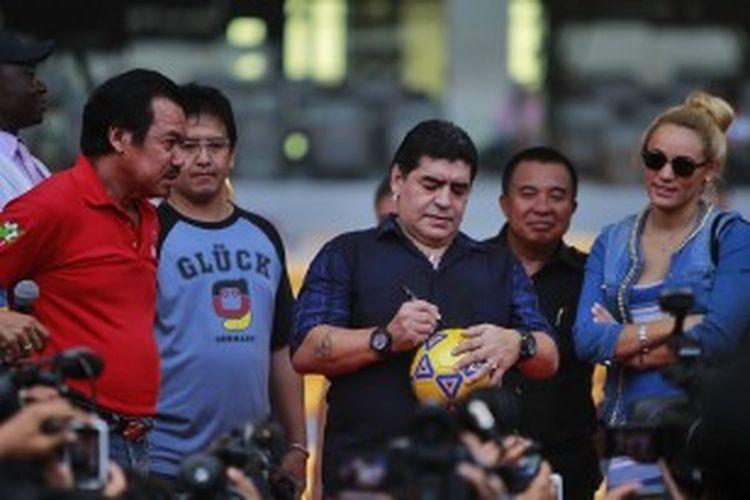 Bintang sepak bola legendaris Argentina, Diego Maradona menandatangani bola yang akan diberikan kepada penggemarnya di Stadion Gelora Bung Karno, Jakarta Selatan, Sabtu (29/6/2013). Dalam rangka kunjungannya ke Indonesia, pemain yang mengantar Argentina menjadi juara Piala Dunia 1986 ini rencananya juga akan mengunjungi Surabaya dan Makassar.
