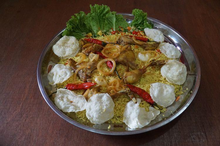 Ilustrasi nasi kebuli ayam di atas piring saji.