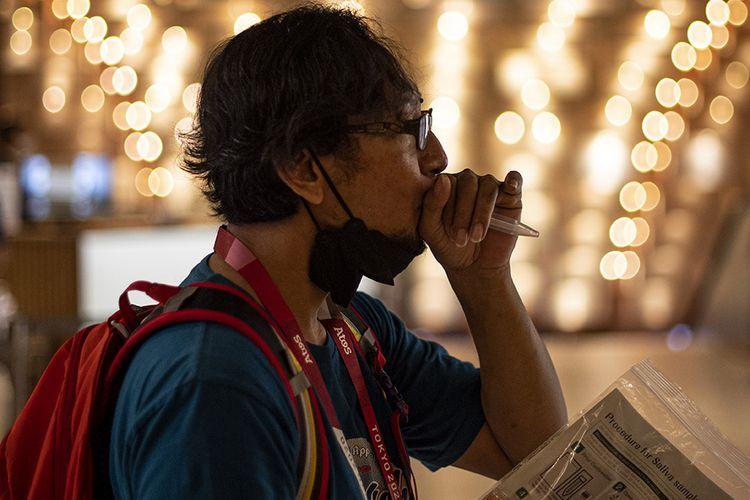 Seorang jurnalis peliput Olimpade Tokyo melakukan tes PCR Covid-19 dengan metode saliva di Shinjuku, Tokyo, Jepang, Senin (19/7/2021). Para jurnalis peliput Olimpiade Tokyo 2020 setiap harinya harus menjalani test PCR dengan metode saliva selama masa karantina tiga hari setelah tiba di Jepang.