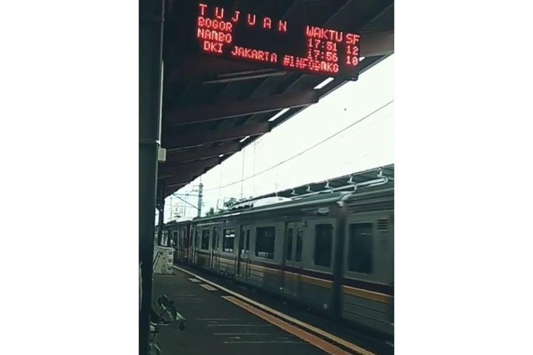 Tangkapan layar dari papan pengumuman keberangkatan kereta api di Stasiun Depok yang menampilkan informasi cuaca dari BMKG.