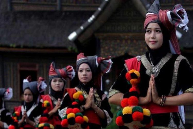 Perempuan menggunakan pakaian adat Sumatera Barat saat penyambutan tamu di garis finish etape tiga Tour de Singkarak 2013 di Istano Basa Pagaruyung, Nagari Pagaruyung, Kabupaten Tanah Datar, Sumatera Barat, Selasa (4/6/2013).