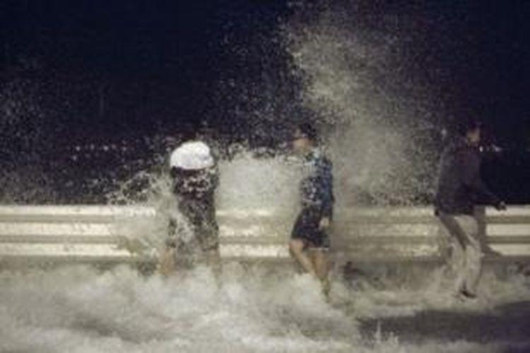 Gelombang yang ditimbulkan oleh topan Usagi menerpa jalan raya di Hong Kong.
