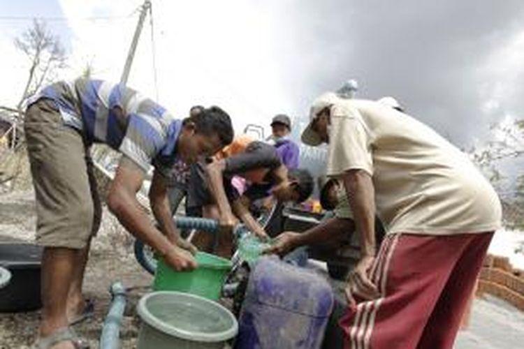 Suasana pembagian air bersih di Desa Laharpang, Kediri, Jawa Timur, Jumat (22/2/2014). Meletusnya Gunung Kelud pada pekan lalu mengakibatkan sejumlah warga yang sudah mulai kembali ke rumahnya mengalami kesulitan air bersih.