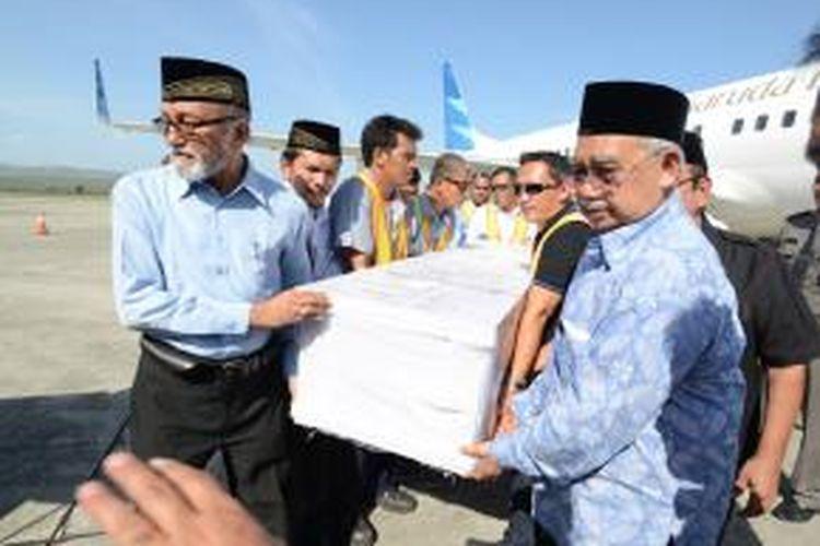 Gubernur aceh, Zaini abdullah ikut mengangkut peti jenazah warga Aceh yang menjadi korban kapal karam di malaysia, yang tiba di Aceh, Minggu (22/6/2014).