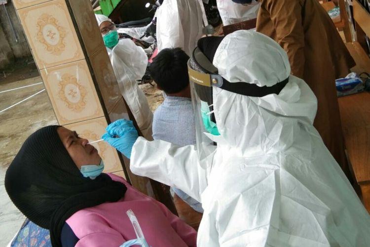 Petugas medis saat melakukan swab test antigen terhadap seorang pengungsi korban tanah longsor di Desa Cibokor, Cibeber, Cianjur, Kamis (17/6/2021). Hasilnya, sebanyak 56 orang terkonfirmasi positif Covid-19.