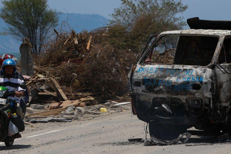Mobil dibakar warga setelah kedapatan melakukan pencurian di Dupa Tondo, Kelurahan Layana, Kecamatan Mantikulore, Kota Palu, Sulawesi Tengah, Selasa (2/10/2018). Pasca gempa dan tsunami di Palu dan Donggala, warga diresahkan oleh maraknya aksi penjarahan dan pencurian.