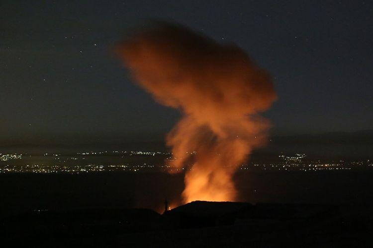Kobaran api dan kepulan asap setelah serangan oleh pasukan pemerintah Suriah di kota Khan Sheikhun, provinsi Idlib, Suriah, Minggu (2/6/2019) malam. (AFP/ANAS AL-DYAB)