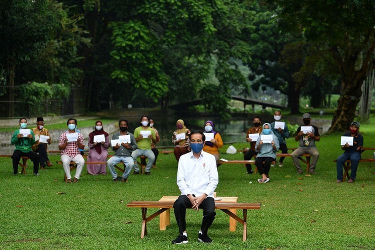Presiden Joko Widodo berfoto bersama penerima bantuan modal kerja di Istana Bogor, Jawa Barat, Rabu (15/7/2020). Presiden kembali menyerahkan bantuan kepada para pedagang kaki lima, keliling, rumahan hingga pedagang asongan masing-masing sebesar Rp2,4 juta sebagai tambahan modal kerja di tengah kondisi pandemi COVID-19. ANTARA FOTO/Sigid Kurniawan/POOL/foc.
