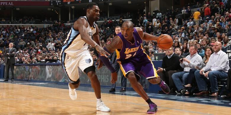 Pebasket Los Angeles Lakers, Kobe Bryant (kanan) mencoba melewati pemain Memphis Grizzlies pada laga lanjutan kompetisi NBA di FedExForum in Memphis, Tennessee, Selasa (17/12/2013).