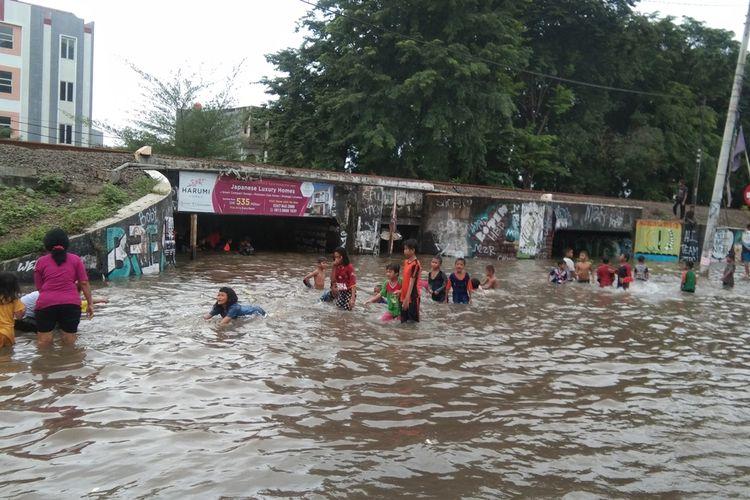 Anak-anak bermain air banjir di Underpass Gonggo, Dusun Jatirasa Tengah, Kelurahan Karangpawitan, Kabupaten Karawang, Sabtu (20/2/2021).